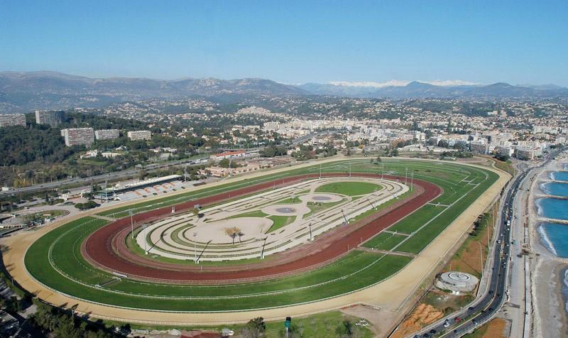 Vue d'ensemble d'un hippodrome et de ses différentes infrastructures : pistes, tribunes, corde, etc.